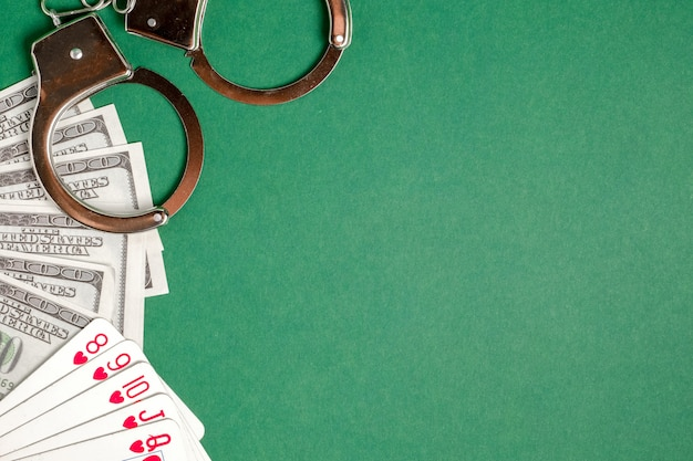Handcuffs lie next to playing cards and us dollars on a green background