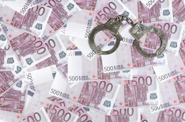 Наручники на фоне пятьсот евро. финансовая преступность, грязные деньги и концепция коррупции - 500 денежных купюр и грязные стальные наручники