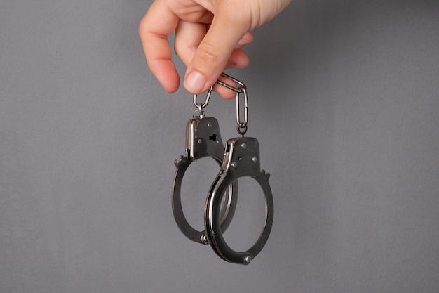 灰色の背景に手錠、犯罪の罰。