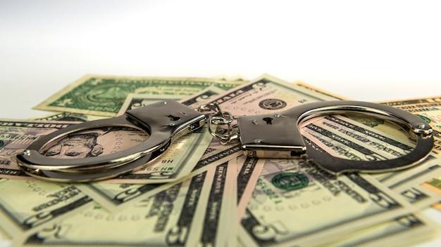 Наручники на денежном фоне, долларовые купюры, коррупция за наличные деньги, финансовые преступления грязных денег и металлические полицейские наручники, выборочный фокус