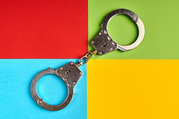 유명한 컴퓨터 회사의 색상으로 종이에 수갑을 채우고 사이버 범죄자는 개념을 잡았습니다. 소프트웨어 회사 로고. 빨강, 초록, 파랑, 노랑 종이 색상. 추상적인 배경입니다.