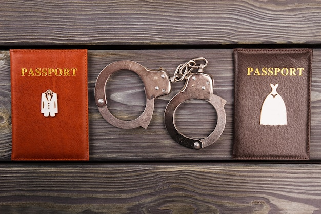 Handcuffs and passports on wood. marriage crime concept.