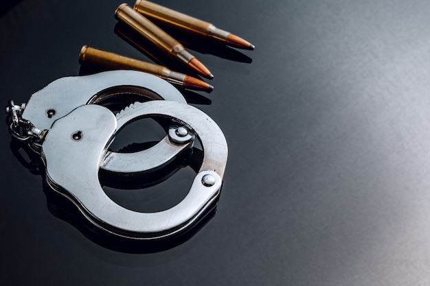 Handcuffs and rifle bullets on black background close up