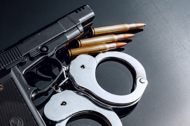 Handcuffs and rifle cartridges on black background