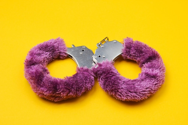 Handcuffs for sex games on yellow background. sexual bdsm toy. fetish, erotic concept.