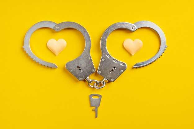 Handcuffs smile shape on yellow background. freedom concept. imprisonment, deprivation of liberty and apprehend perpetrators.