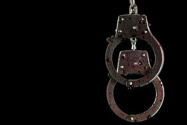 Handcuffs were hung and droplets of fake blood in darkness background