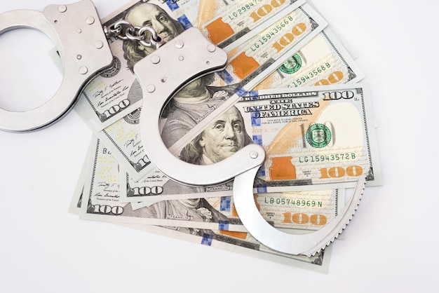 Наручники с долларами на белом фоне.