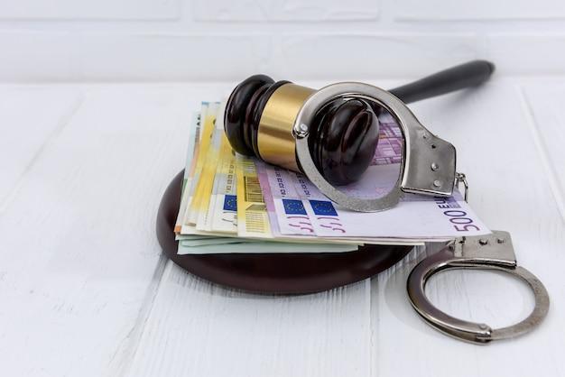 Наручники с банкнотами евро и молоток судьи