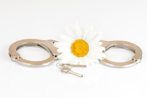 Handcuffs with keys and a white flower
