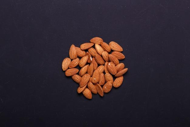 Handful of almonds on a black slate - healthy snack.