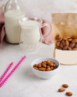 A handful of almonds in close-up, next to a package of nuts with space for text and logo