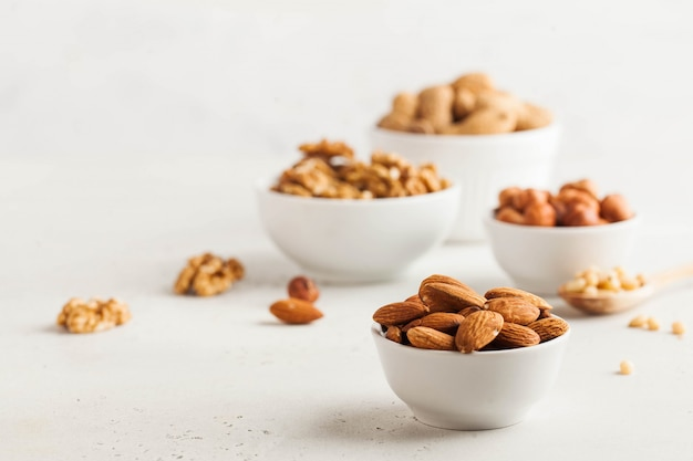 A handful of almonds in a white bowl, assorted nuts on a light background. healthy snacks, healthy fats. copy space.