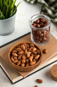 A handful of almonds in a wooden plate and hazelnuts in a glass jar on a light background and a green plant in the back the background