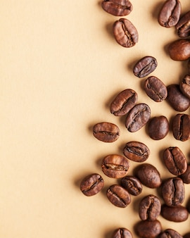 A handful of arabica coffee beans on a light brown background. vertical photo with place for text for coffee houses, screensavers, roasters and coffee makers.