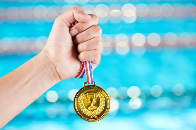 Handful of asian man holding gold medal with blurry background of swimming pool.