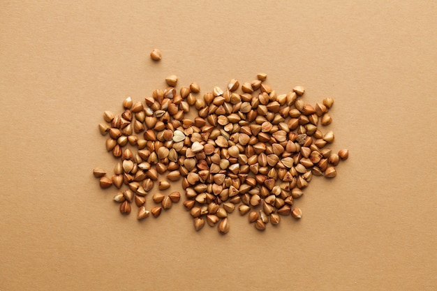 A handful of buckwheat groats on a brown surface