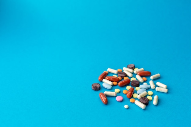 A handful of colored pills spilled on a blue table. medical concept.