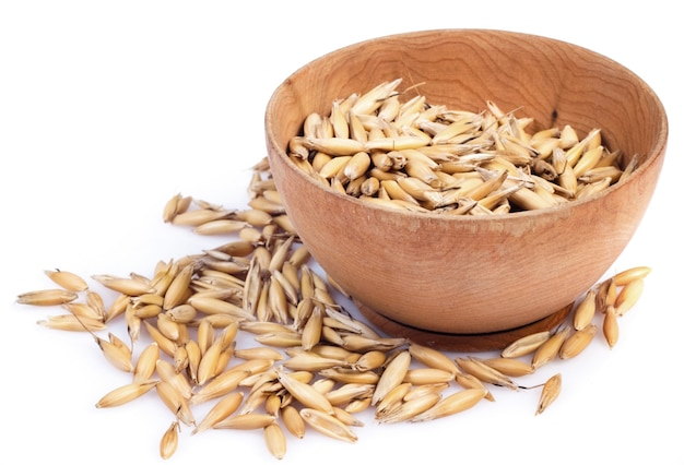 Handful of crops of oats in the wooden saucer on a white surface