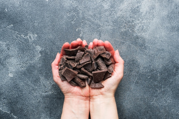 A handful of crushed dark chocolate in women's hands palms on a dark textured background.