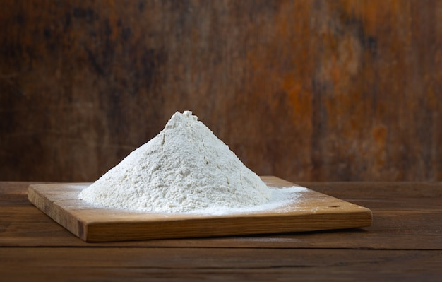 Handful of flour on wooden table