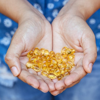 Handful of gel capsules of omega 3. close up capsules of fish oil in girl hand.