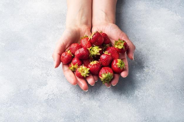 コンクリートの背景の手に一握りのジューシーな熟したイチゴ。甘くてヘルシーなデザート、ビタミンの収穫。コピースペース。