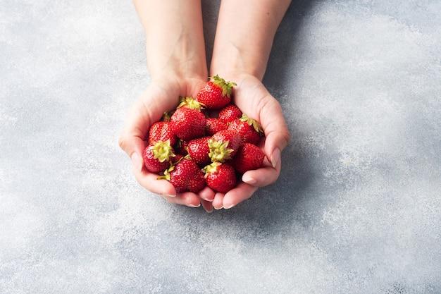コンクリートの背景に手に一握りのジューシーな熟したイチゴ。甘くてヘルシーなデザート、ビタミンの収穫。コピースペース。