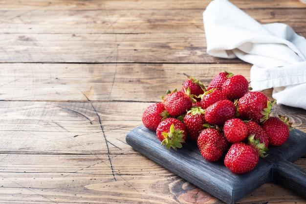 木製の素朴な背景に一握りのジューシーな熟したイチゴ。甘くてヘルシーなデザート、ビタミンの収穫。コピースペース。
