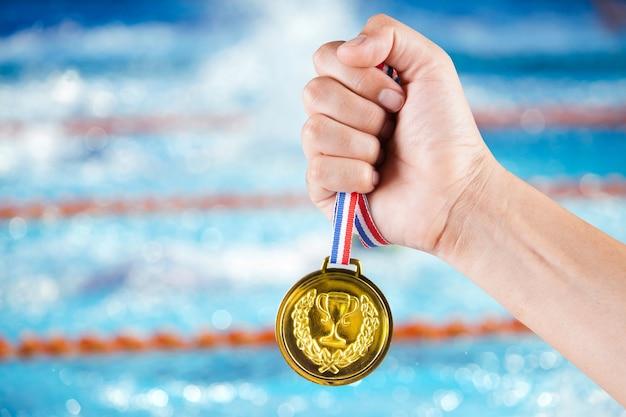スイミングプールと水泳競争のぼやけた背景で金メダルを保持する少数のアジア人。