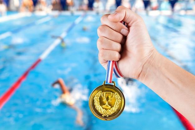 スイミングプールのぼやけた背景で金メダルを保持しているアジア人の一握り。