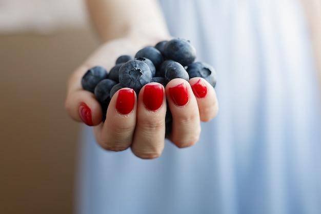 Горсть черники выливается из женских рук