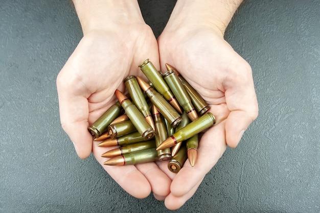 남자의 손에 kalashnikov 돌격 소총을위한 소수의 녹색 7.62mm 카트리지. 평면도
