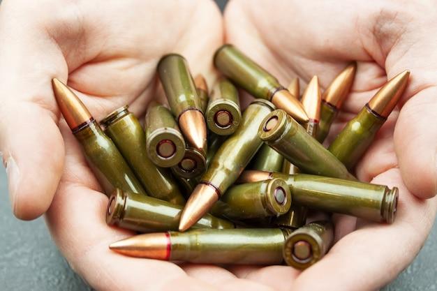 남자의 손에 kalashnikov 돌격 소총을위한 소수의 녹색 7.62mm 카트리지.