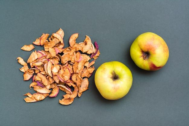 Горсть кусочков сухих яблок и свежих яблок на зеленом фоне. вид сверху