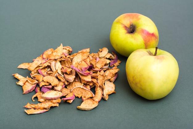 Горсть кусочков сухих яблок и свежих яблок на зеленом фоне
