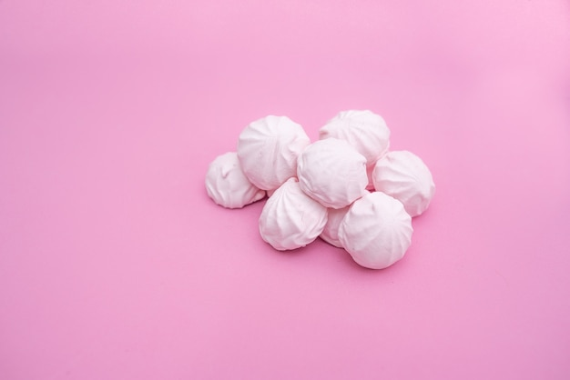 Горсть маленьких зефиров на розовом фоне