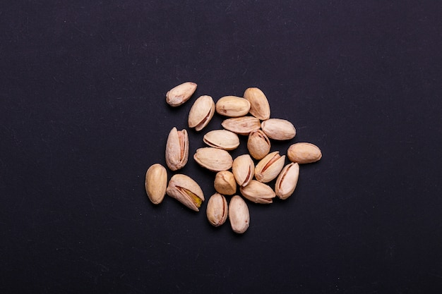 Handful of pistachios on a black slate - healthy snack.