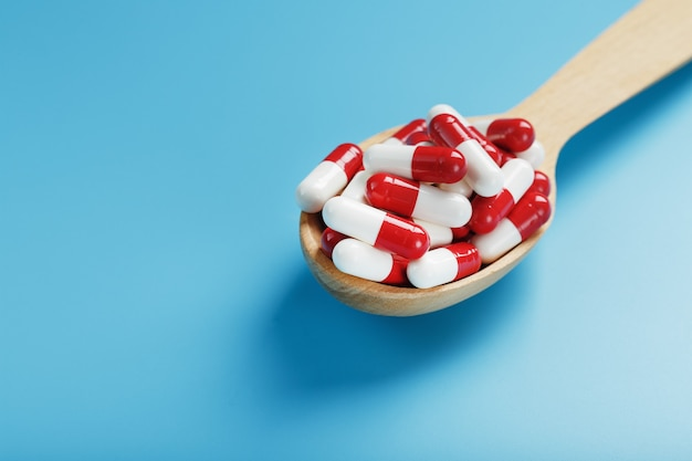 A handful of red and white pill capsules in a wooden spoon on a blue background