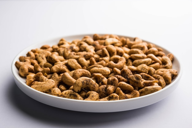 A handful roasted spiced cashew nuts  or masala kaju served in a bowl, selective focus