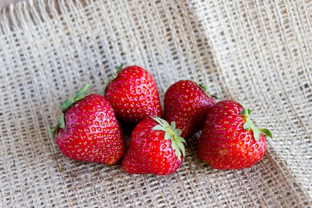 A handful of strawberries on sackcloth, fresh strawberries from the garden