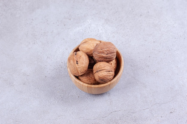 A handful of walnuts piled in a wooden bowl on marble surface