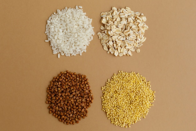 Handfuls of various cereals on brown background. rice and oatmeal, buckwheat and millet