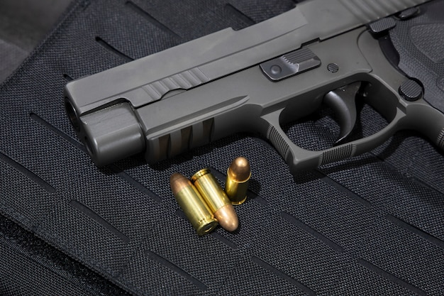 Handgun and 9mm bullets on a bulletproof jacket