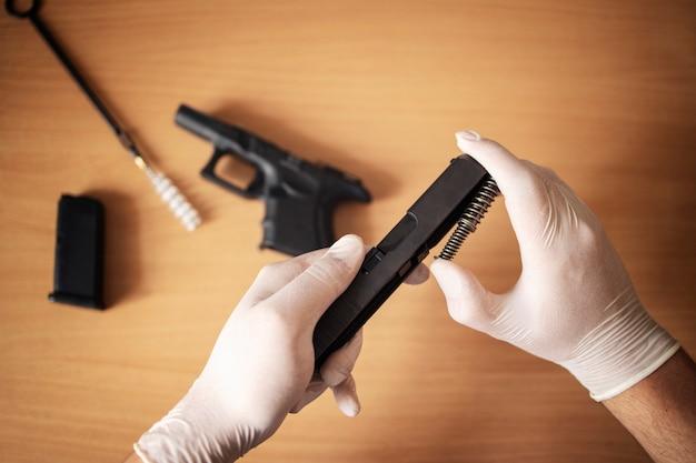 화약 찌꺼기를 청소하기 위해 권총을 부품과 브러시로 분해