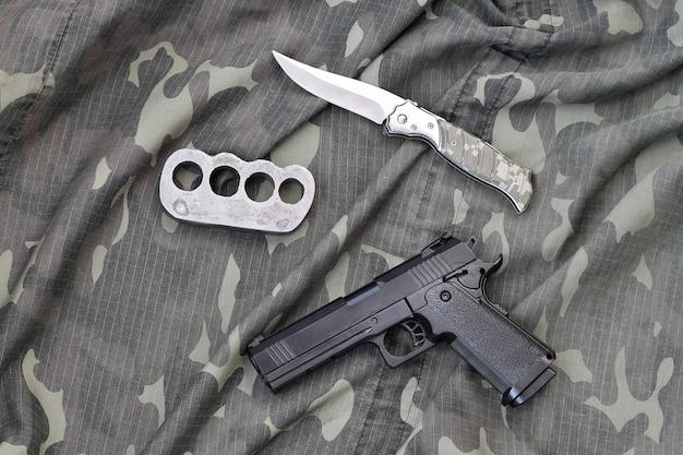Укладка пистолета с кастетами и ножом на камуфляжную военную форму