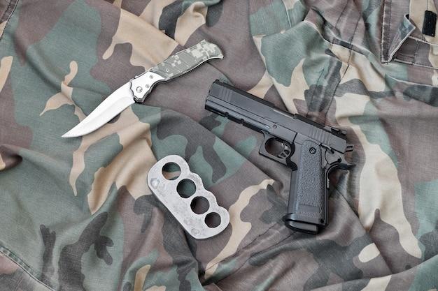 Пистолет лежит с кастетами и ножом на камуфляжной военной форме крупным планом. понятие грабежа и незаконной торговли оружием