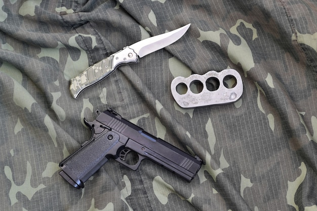Handgun lies with brass knuckles and knife on camouflage military uniform close up. concept of looting and arms trade