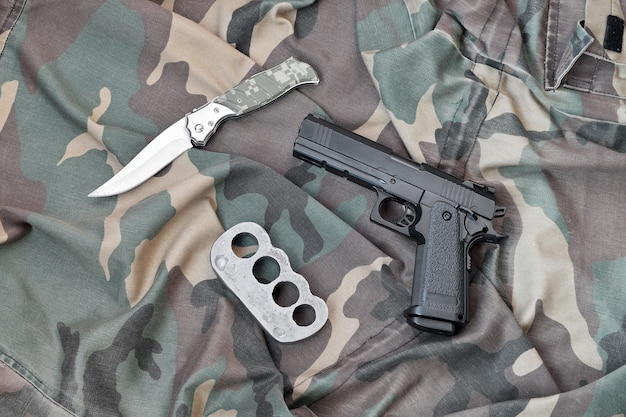 Handgun lies with brass knuckles and knife on camouflage military uniform close up. concept of looting and illegal arms trade