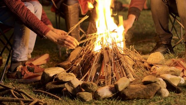 Riprese a mano di un uomo che fa fuoco da campo per i suoi amici in una notte fredda.